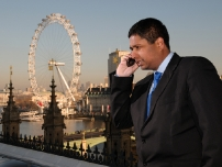 Annesley on the phone overlooking the London Eye from Parliament